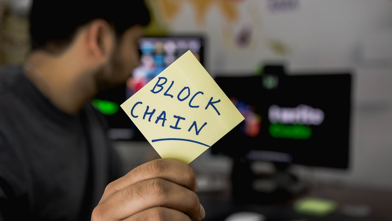 "Man holding a sticky-note with the words ""Block Chain"" written on it, looking at computer screens in the background"