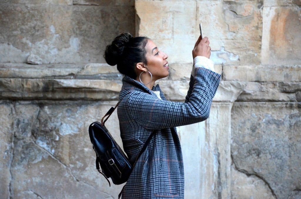 Woman uses her phone to take a photo - she is standing facing to the side of the camera, and is smiling at her phone with a black backpack on.