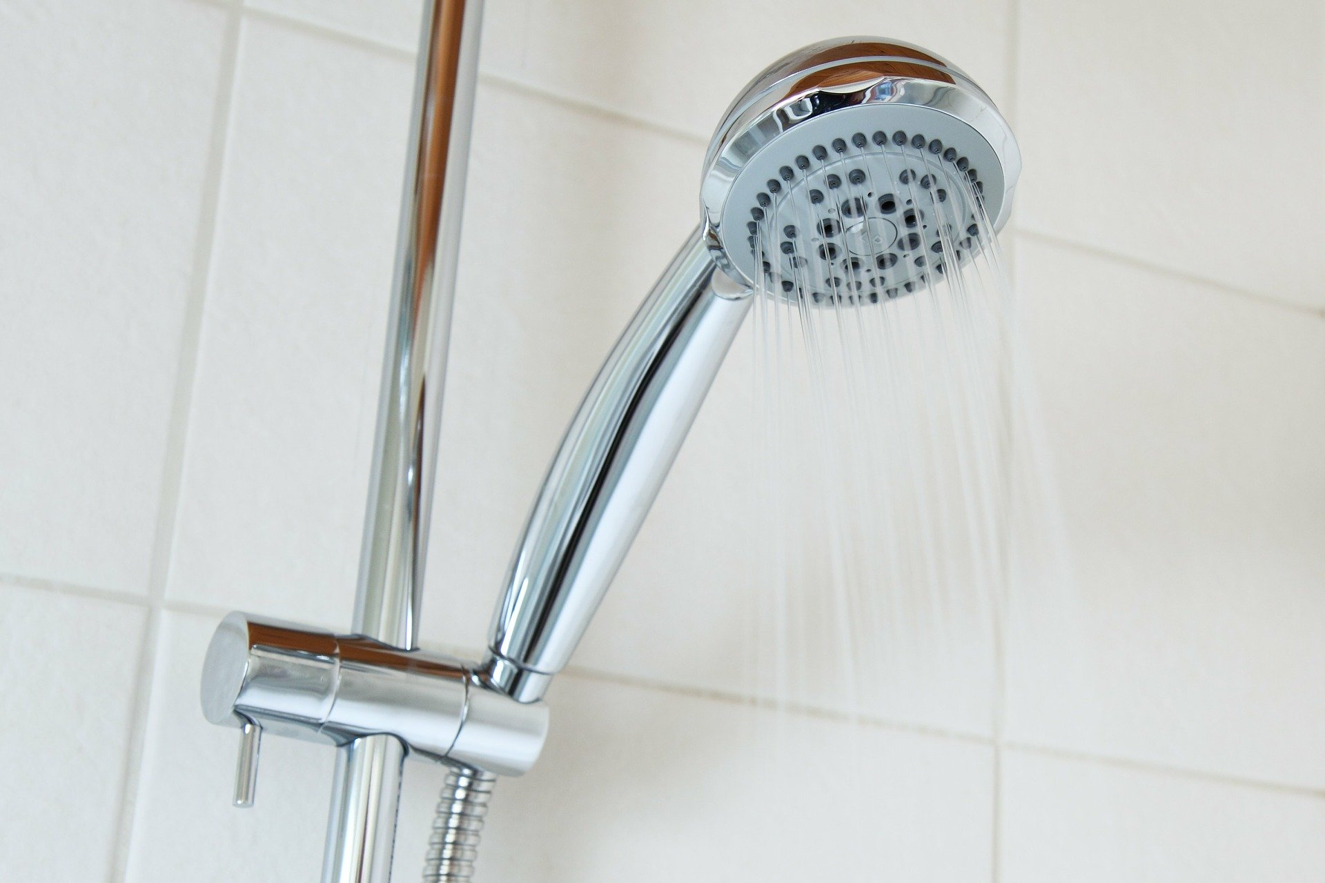 Chrome shower head spraying water, against a back-drop of white tiles