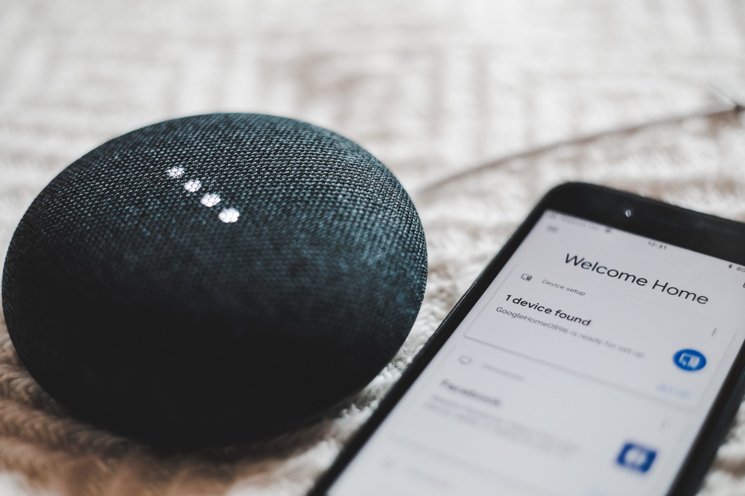 Google home mini voice assistant device next to an Android phone