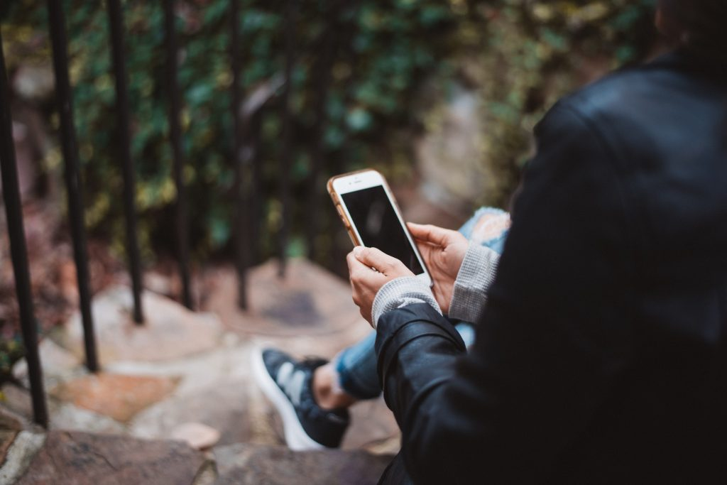 image of person sitting on step using their phone for multiple language apps with a blurred background