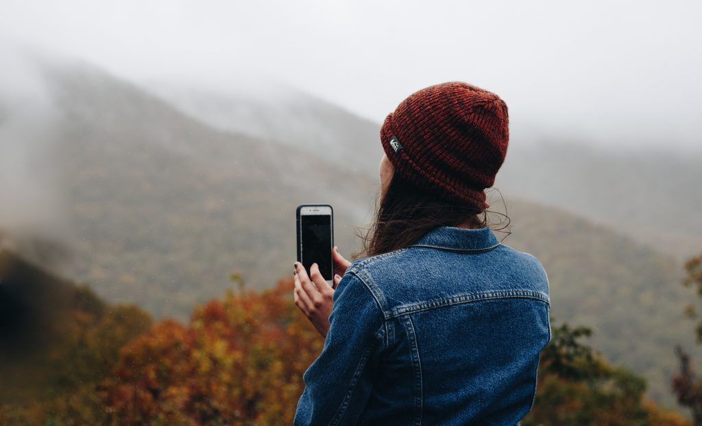 Photo of a woman holding an iPhone - facing away from the camera - in front of an autumnal mountainous landscape.