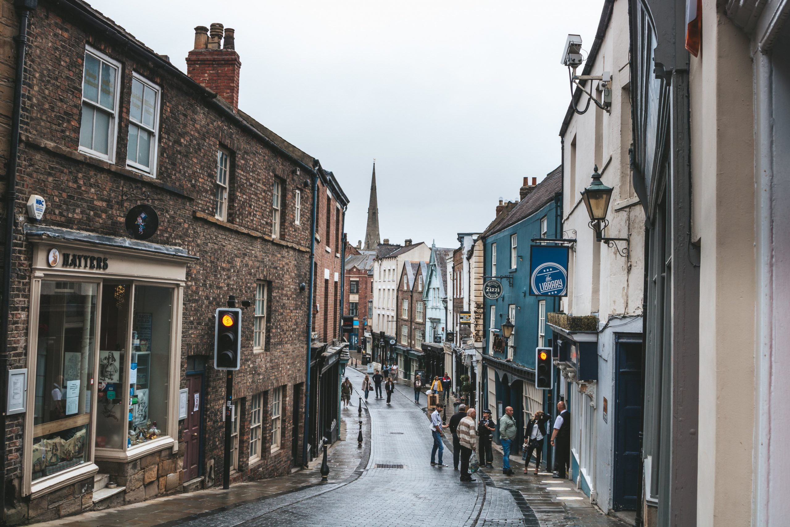 Durham high street - people walk on the street between buildings during the daytime in the rain