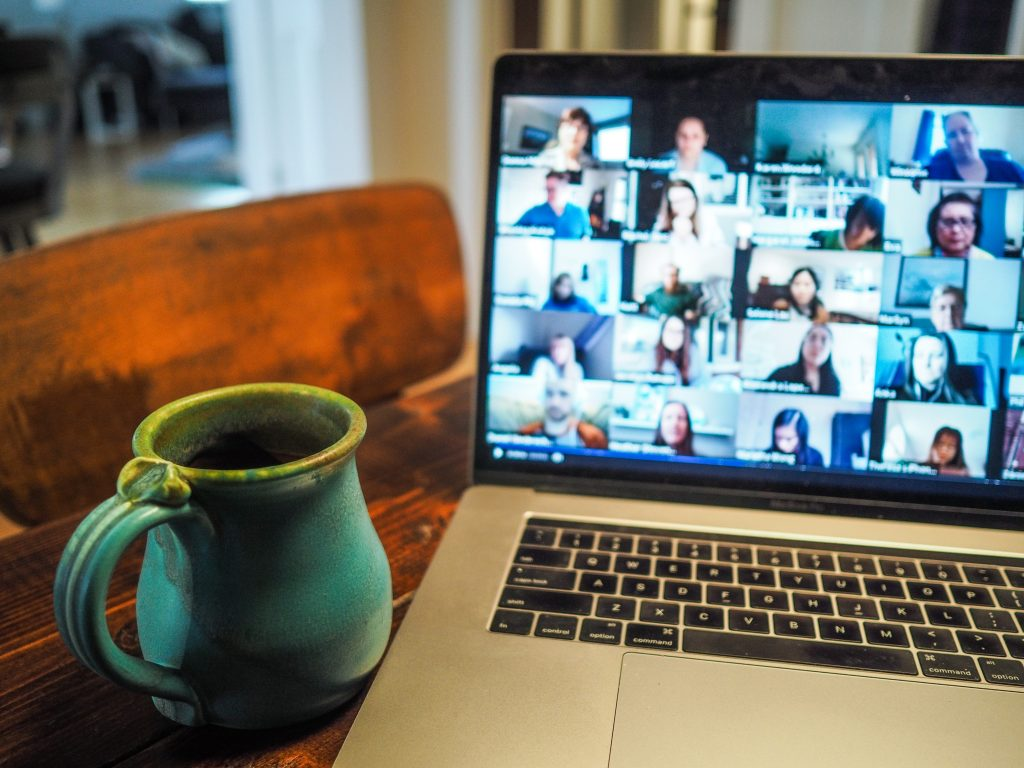 Photo of a blue mug on a desk next to a macbook where a virtual group meeting is taking place