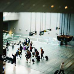 A group of people moving through an airport with luggage, seen from a distance. Signs are shown all around them.