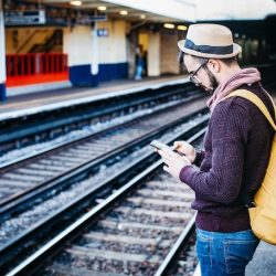 Man wearing a trilby hat and a yellow backpack uses a smartphone on a train platform, with train tracks in the background