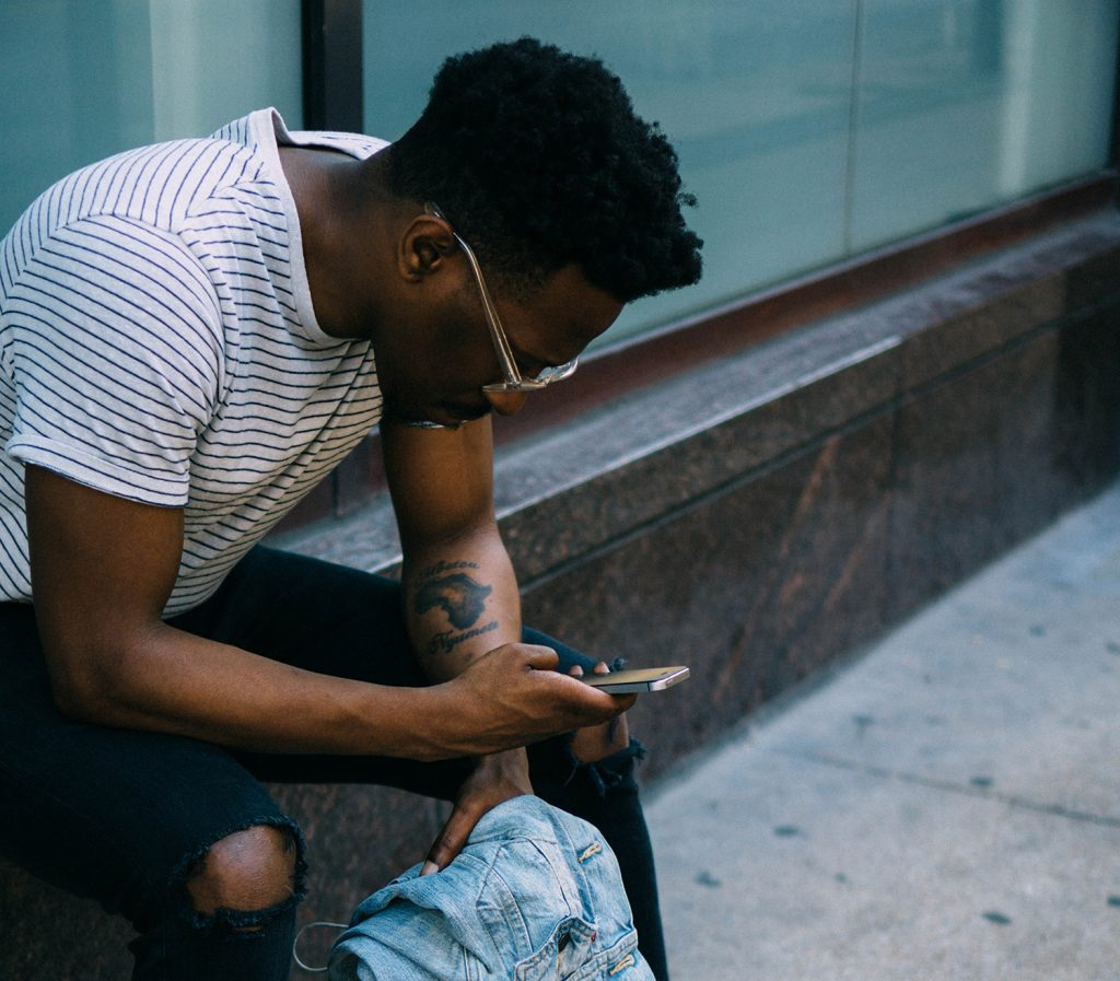 Photo of a man sitting on a wall in front of windows, looking at his phone.