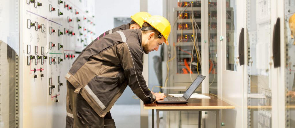 Two engineers in hard hats look at a laptop in a control room, covered in buttons and switches