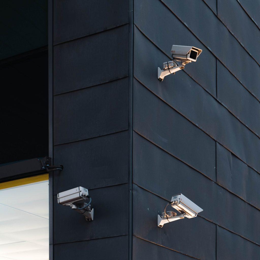 three white cctv cameras on a building
