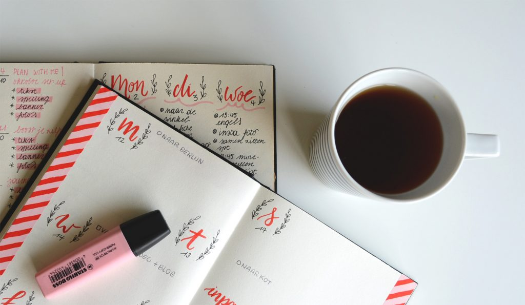A photo taken from above, of a weekly planner book and cup of coffee.