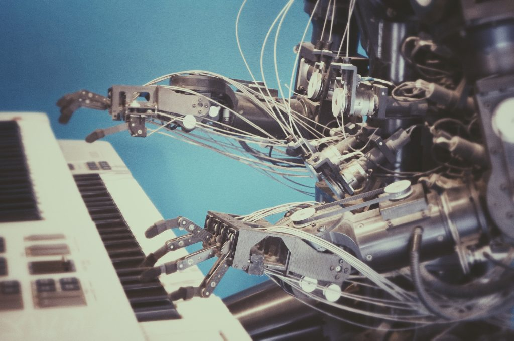 Photo of a metal robot with exposed wires, playing a keyboard in front of a blue wall.