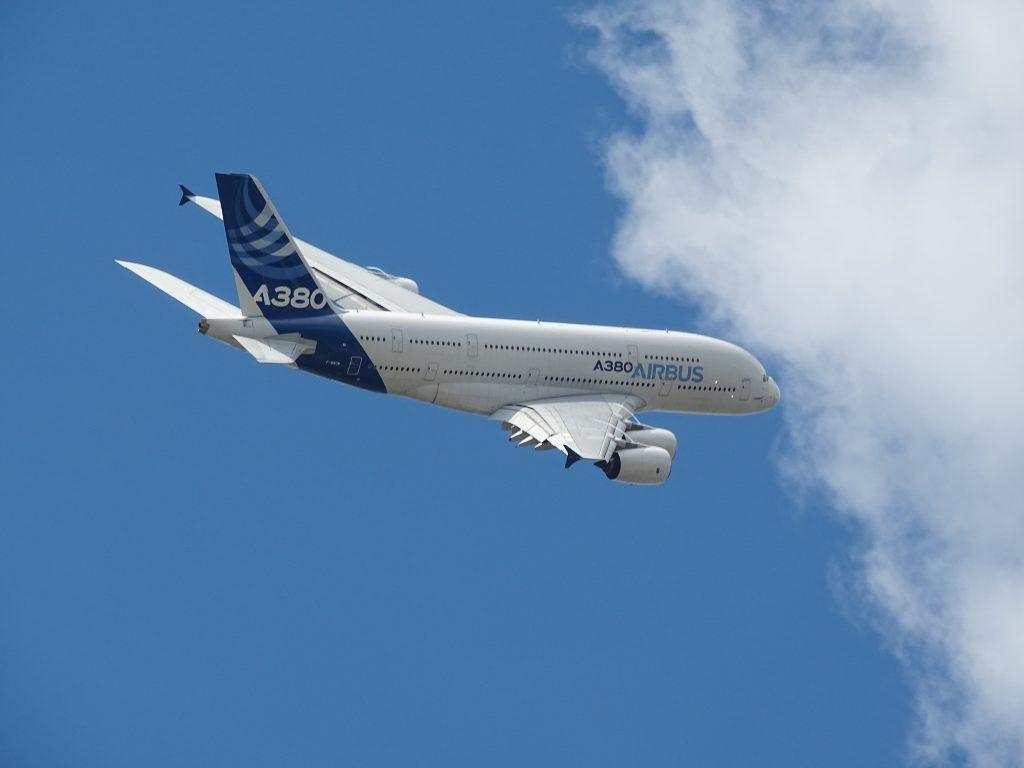 An Airbus A380 flies through a clear blue sky