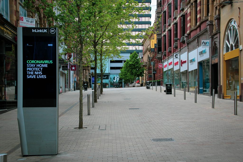 Image shows an empty high street with a digital sign warning the public of coronavirus