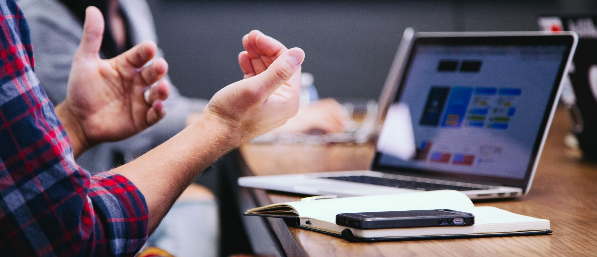 from a low angle, a meeting desk with a phone, notebook, pen & laptop can be seen. to the left, you can see someone's hands who's movements indicate they are explaining someting in a meeting - probably platforms.