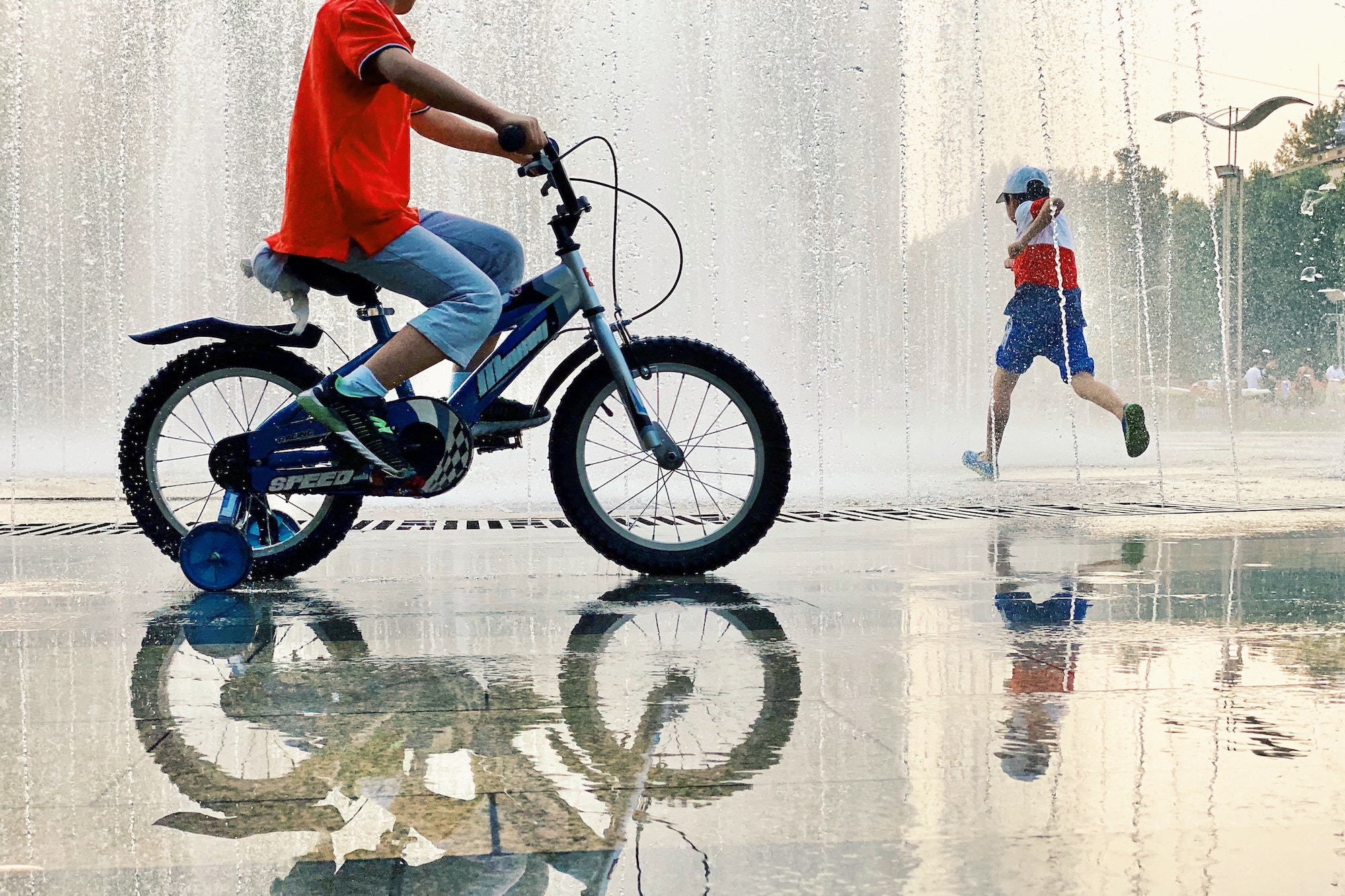 Children running into water fountains, a child on a bike with stabilisers rides in the foreground.