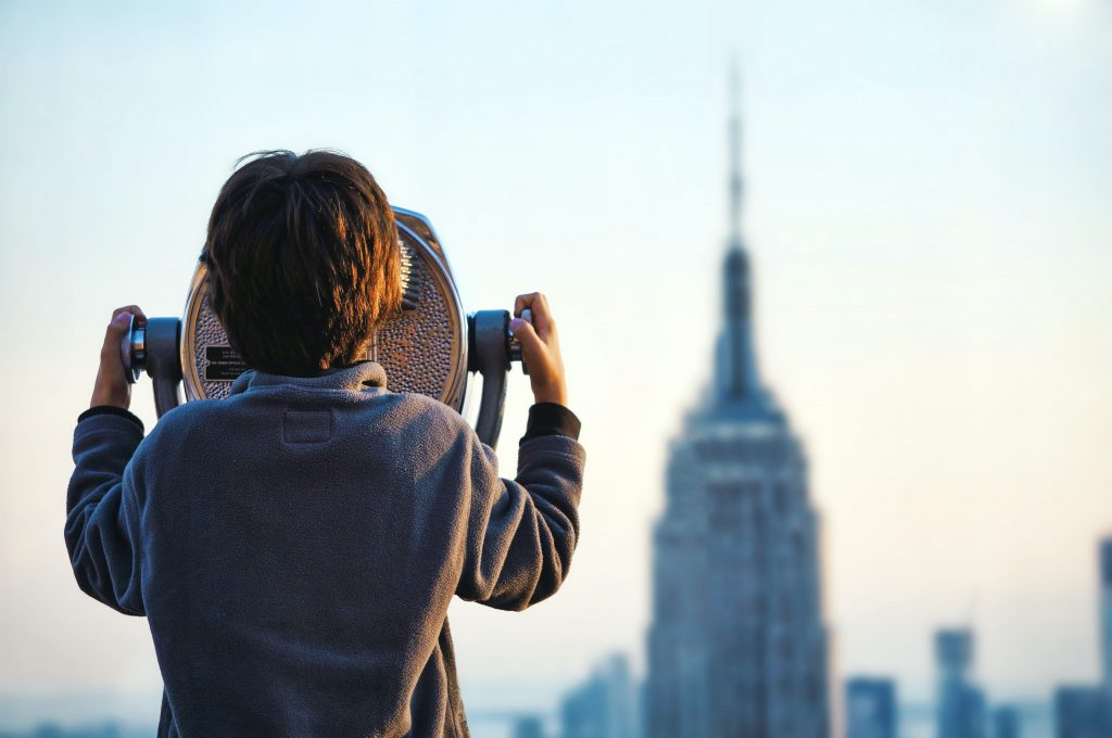 a person looks through binoculars onto a city skyline
