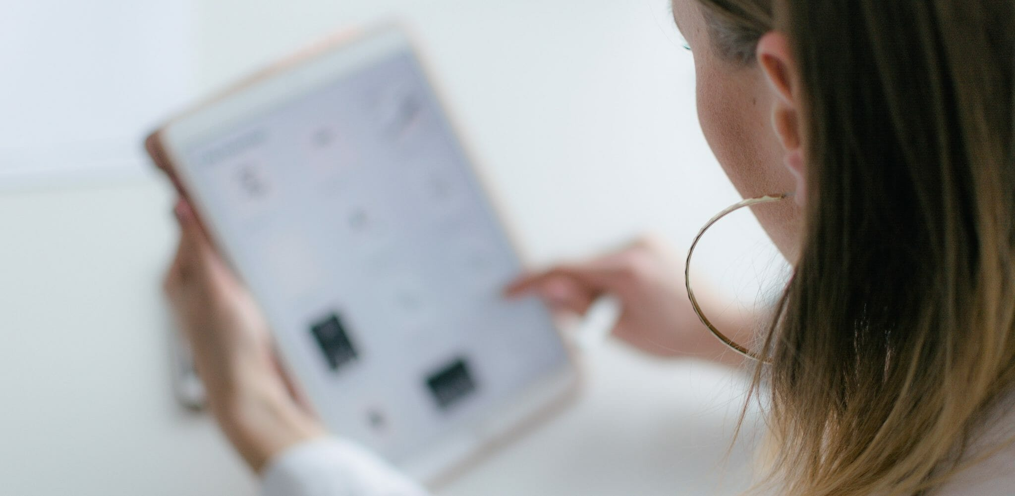 Photo shot looking a girls shoulder, her hair and silver hoop earring and profile of the left side of her face can be seen. She is using a tablet, assuming for a platform, but the focus is on her so the tablet is blurred.