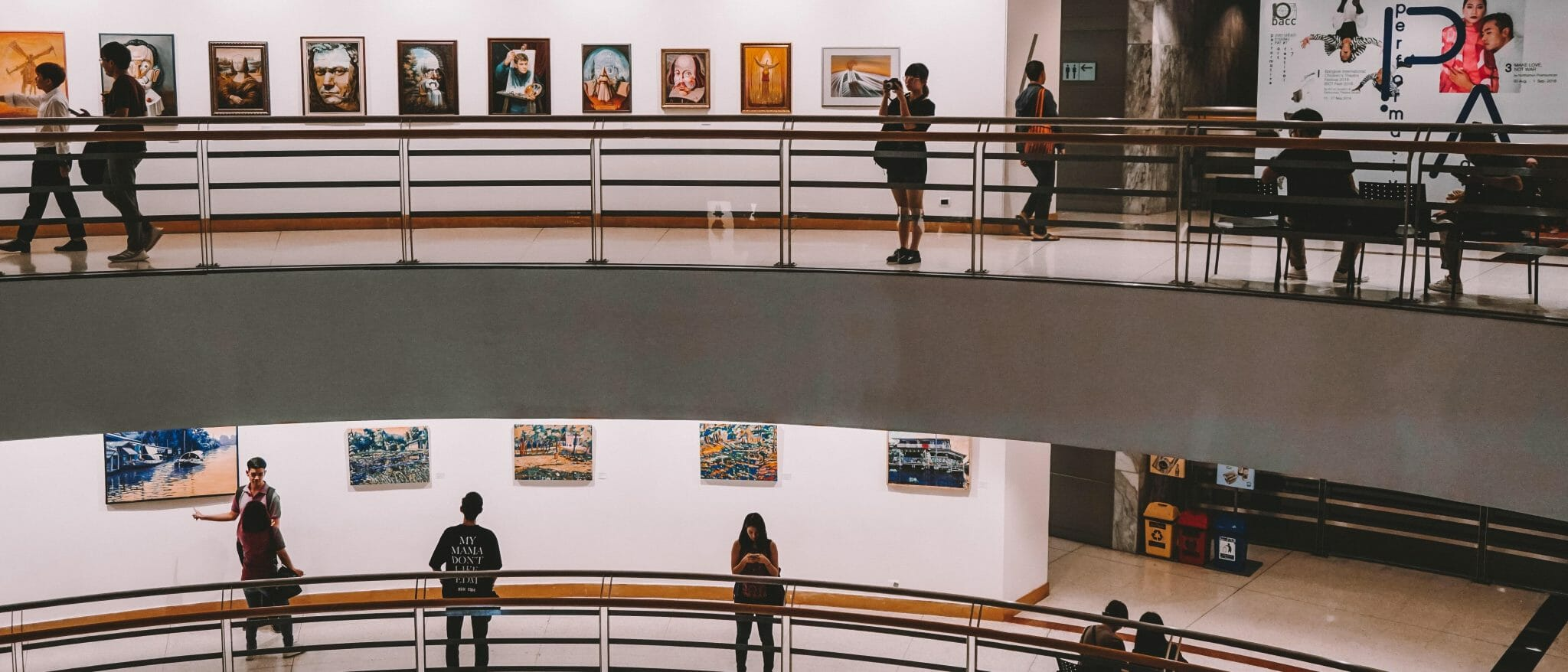 A picture of people in an art gallery with paintings aligned in rows along the walls. On two balcony levels, people are walking, looking at the paintings or taking pictures.