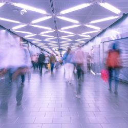 Many people walk in an artificially-lit subway. People are blurred as they move near the camera.