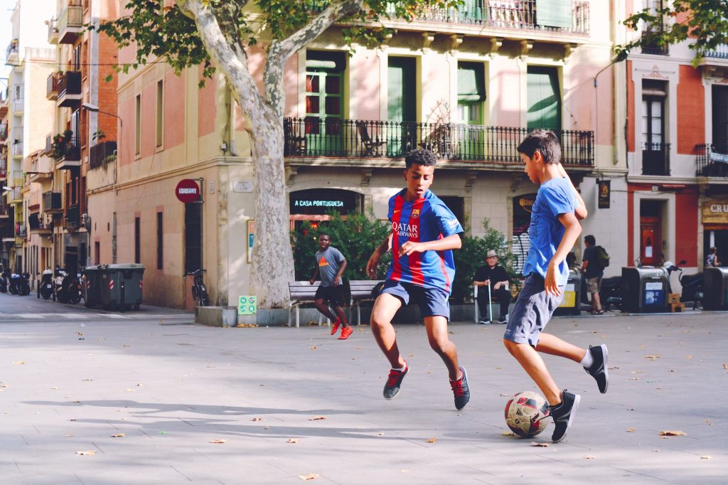 Two children play football in a city plaza.