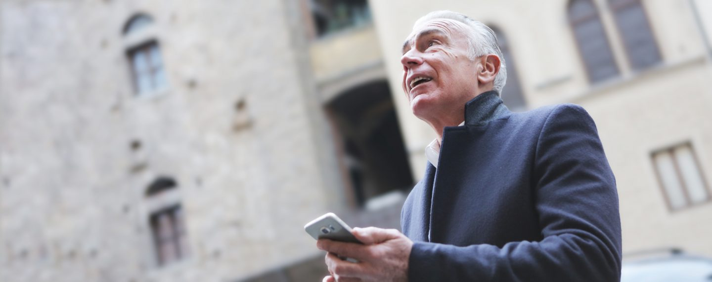 A white man, with grey hair, wearing a grey coat and has headphones in, is holding his phone as he man enjoys a historical tour on the Hidden Cities app - showing how he is enjoying a museum/cultural experience without the boundaries of walls