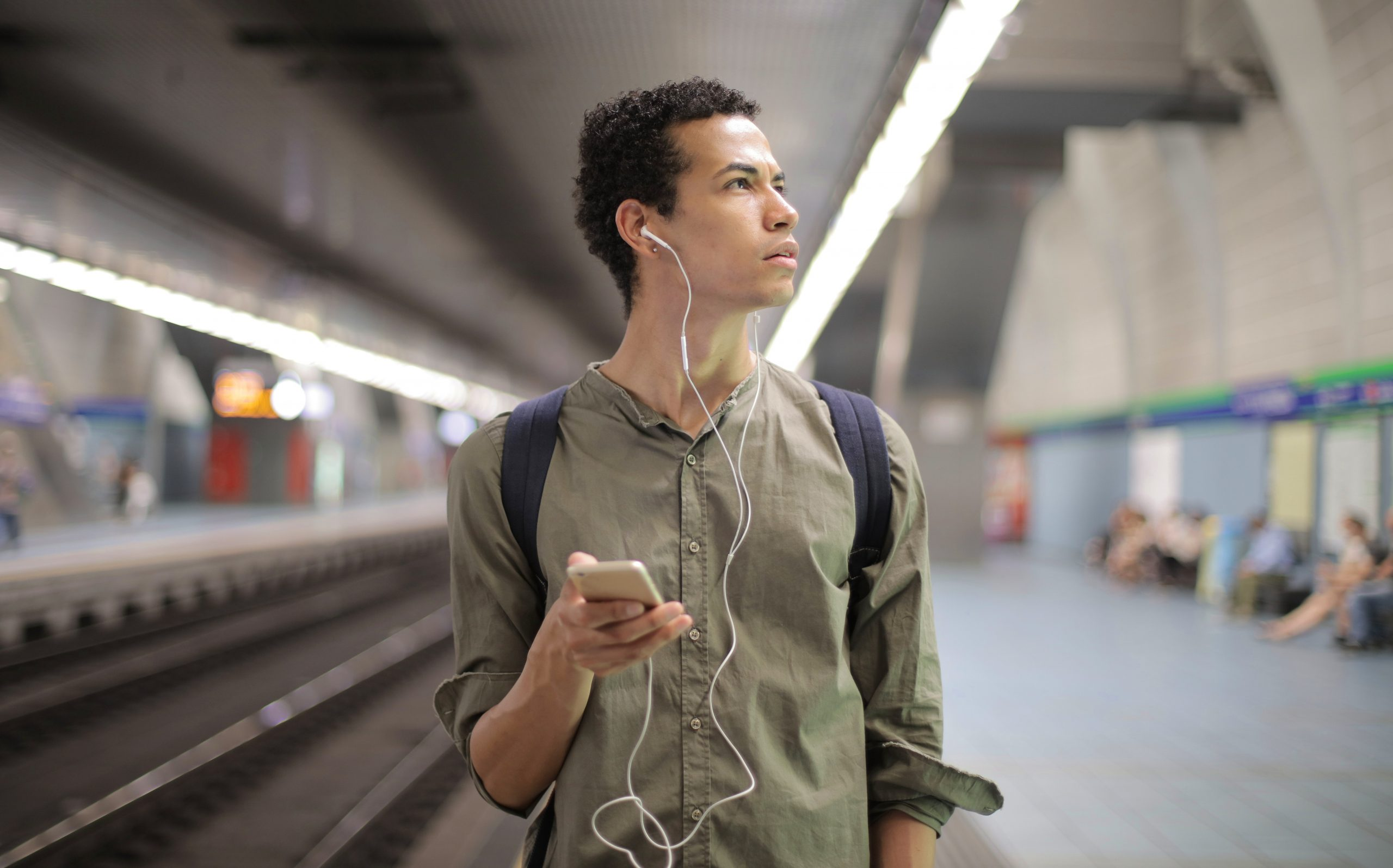 Person with phone and headphones in underground station