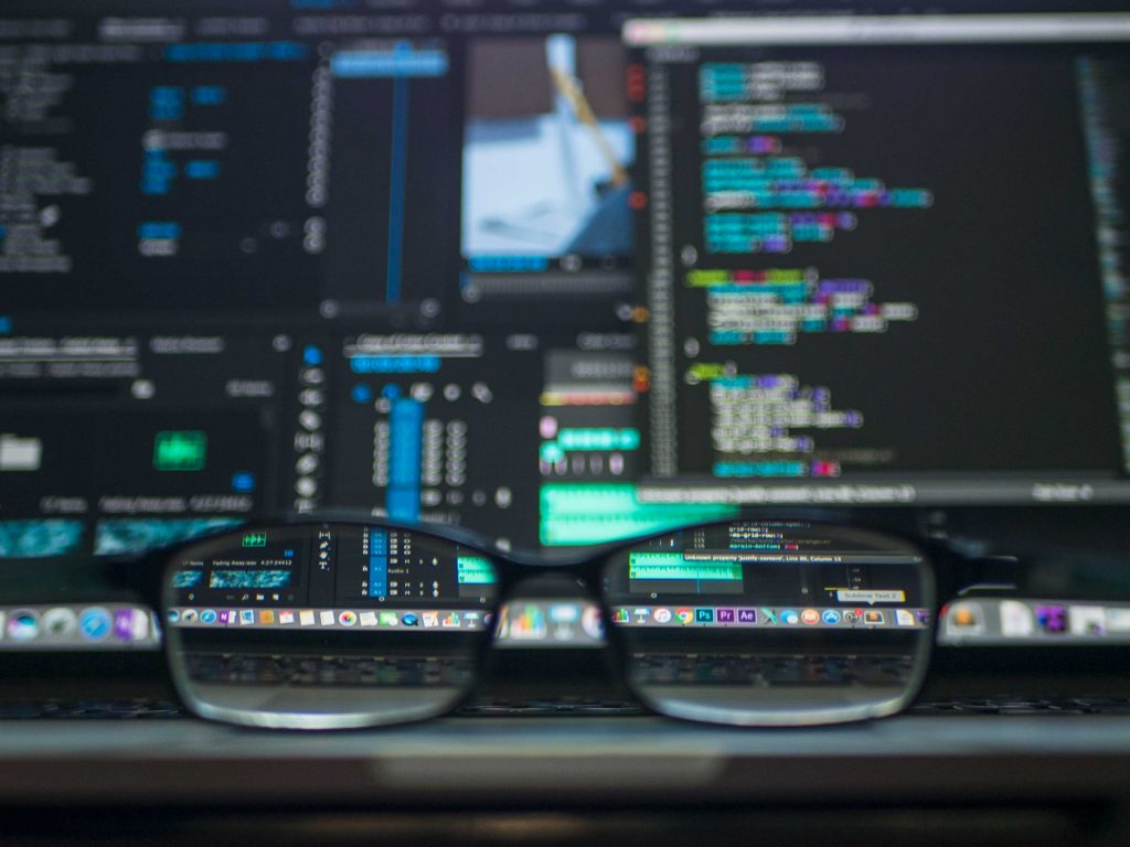 black framed glasses in front of computer, with the computer showing lots of data