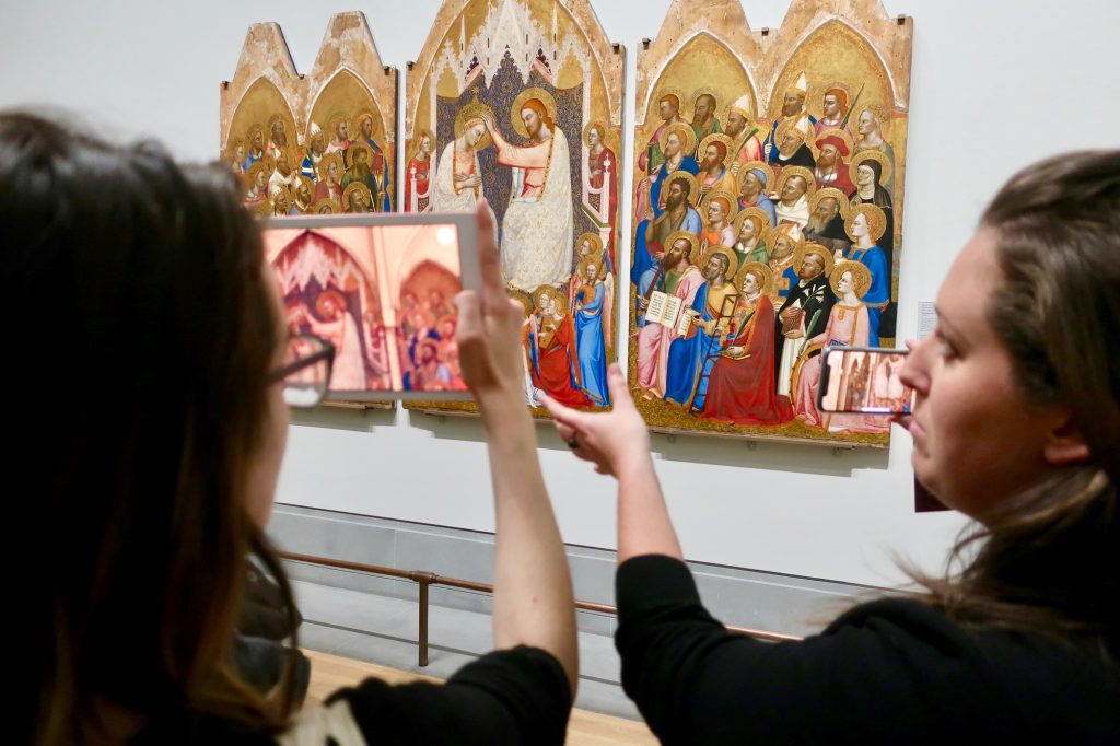 Two women hold a tablet up in-front of a colourful altarpiece hanging on a gallery wall