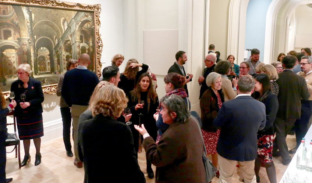 Groups of people talking at a gallery event, with renaissance paintings hanging in the background