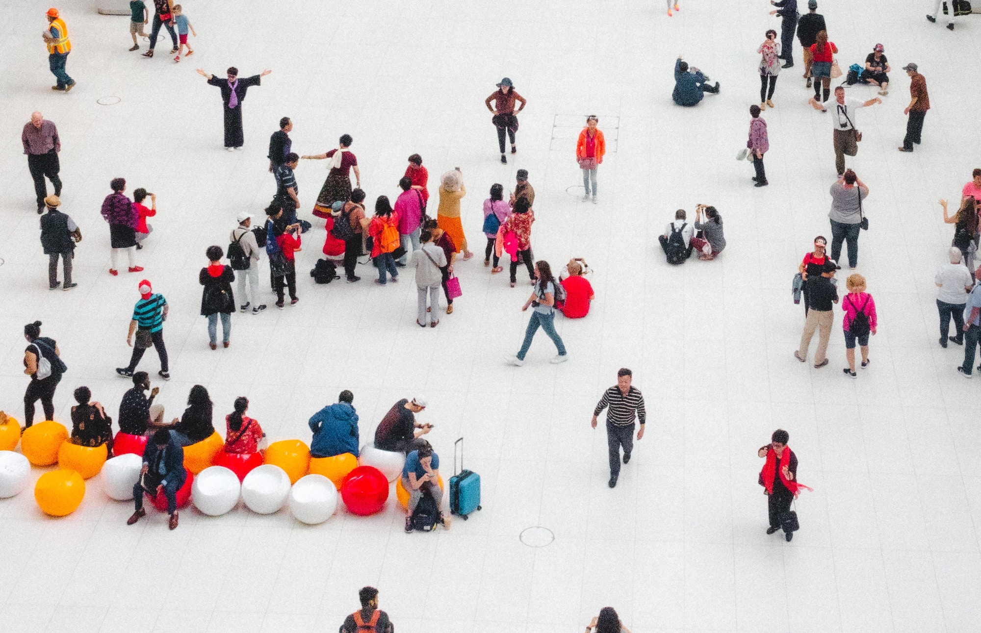 Many people walking across a white-floored public space, seen from above
