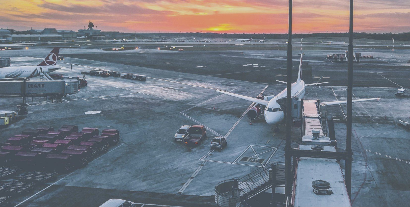 A quiet airfield at sunset, with 2 planes currently parked on the runway and other machinery around them
