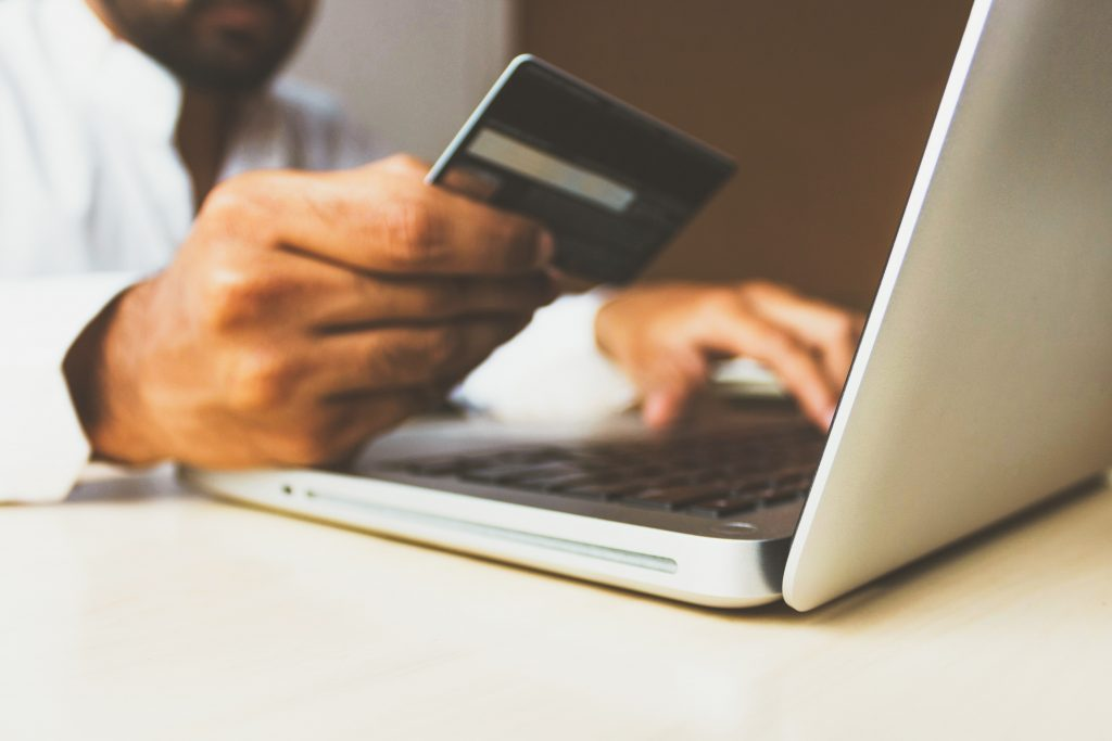 A person uses their laptop while holding their payment card, as if they are ordering something online