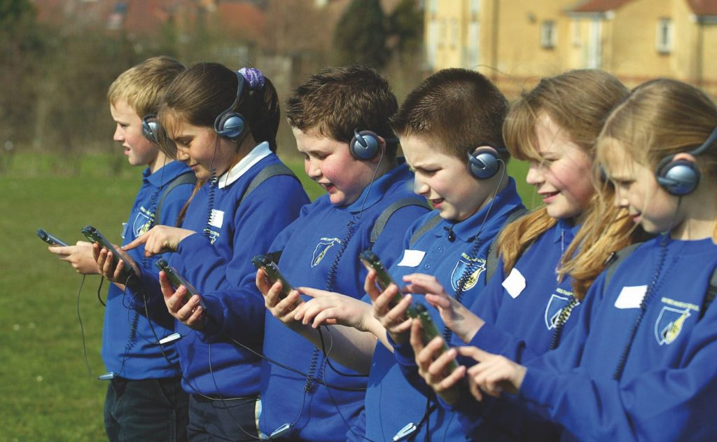 A row of school children in blue uniforms stand with headphones on, and holding GPS devices, at the edge of a playing field.