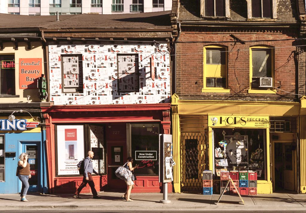 High street with red and yellow painted shop fronts, with people walking in the foreground