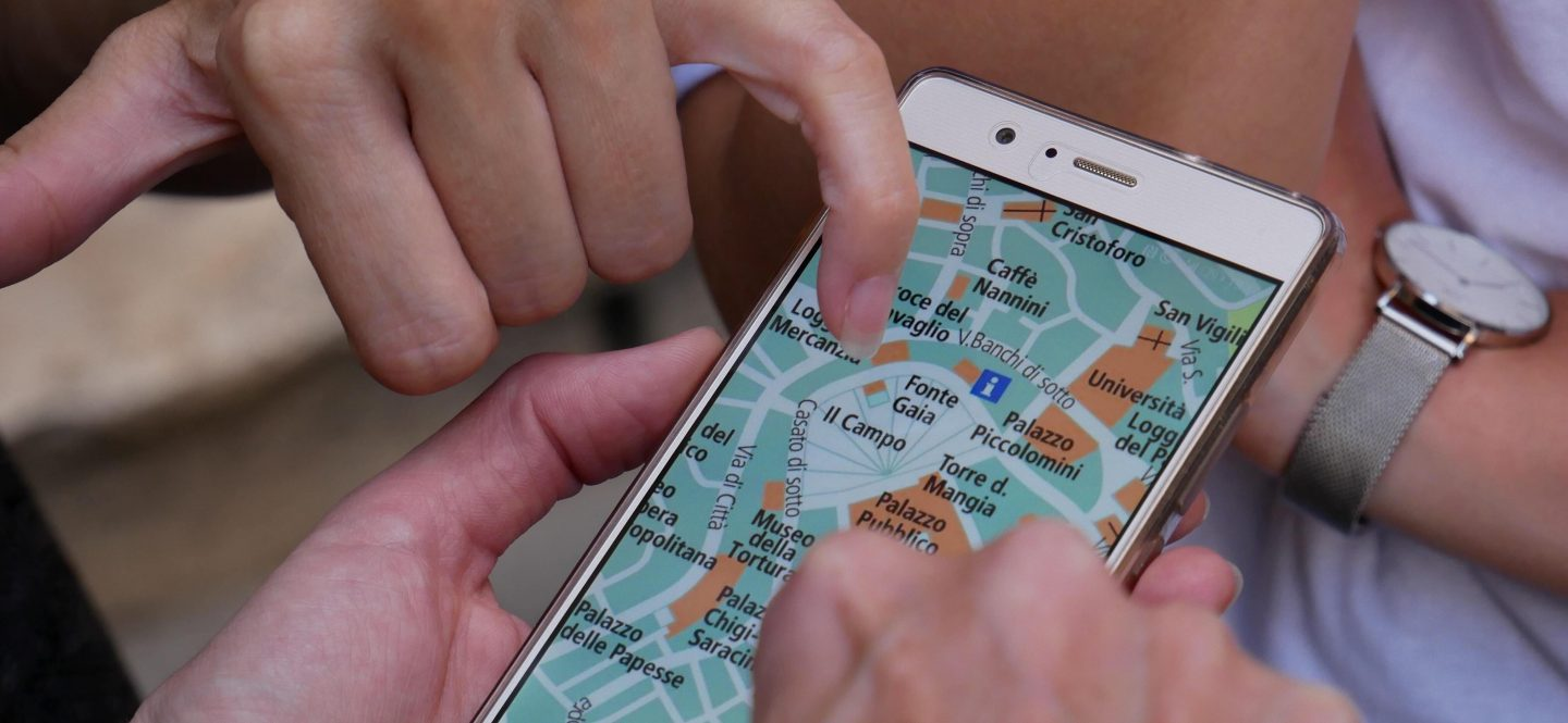 a circle of hands surround a phone with a map on the screen.