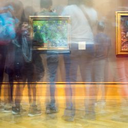A time stop photo shows different people stopping to look at the same painting. The image is here to represent the hybrid museum - people experiencing the same attraction in the museum or from home