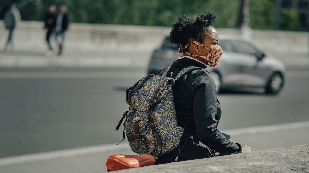 a woman is walking down a street with a backpack on and a colourful face mask