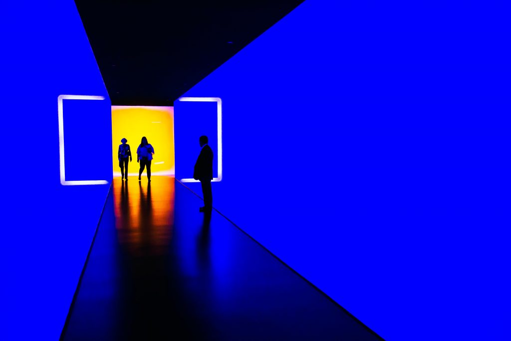 3 people are standing in a corridor that is lit up in vivid blue. they are walking thriugh a doorway that leads to an orange lit room.