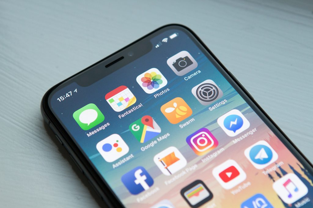 Photo of an iPhone X with the apps visible on its home screen, lying on a grey wooden table.