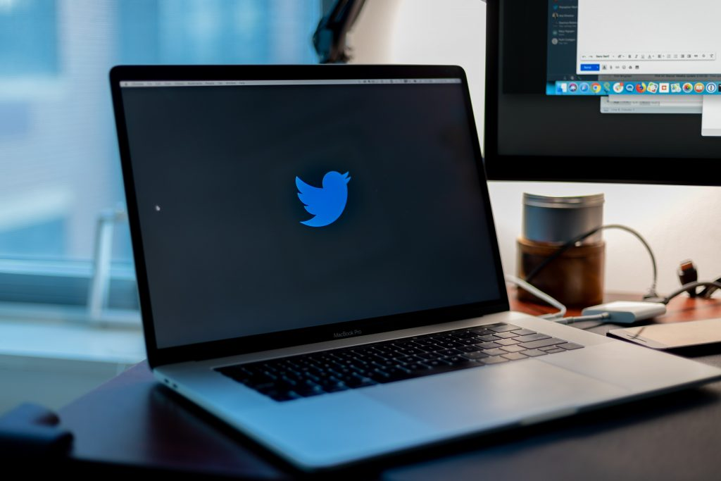 Laptop on a desk showing the Twitter bird logo as a wallpaper
