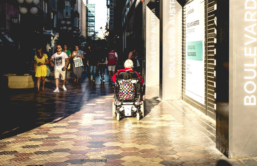 Person in a wheelchair moves along a paved city street, away from the camera.